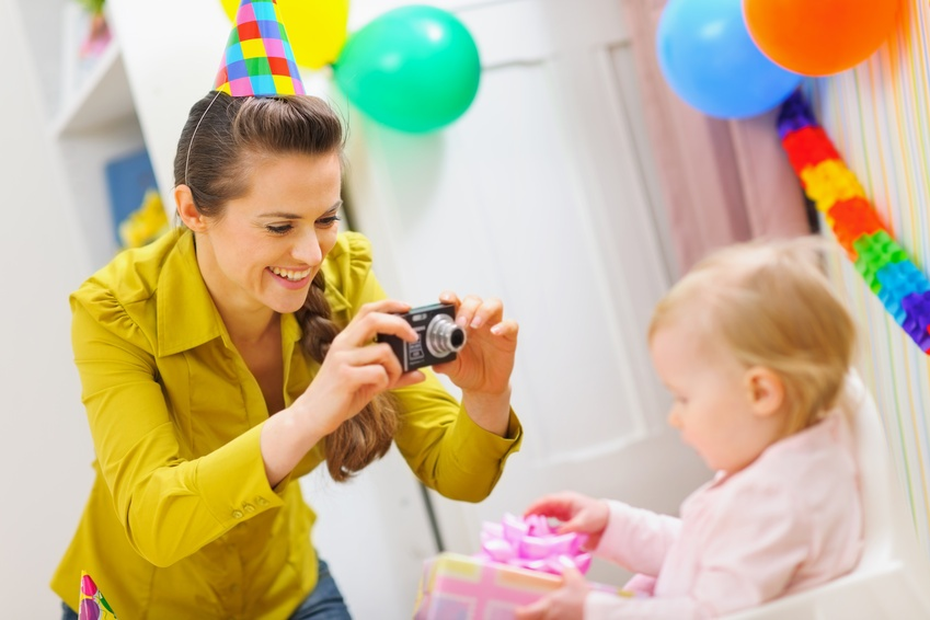 Mother making photos at babies birthday party